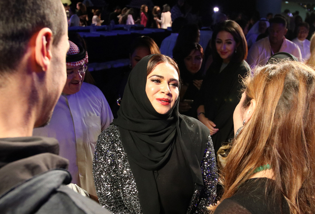 "Emirati fashion designer Lamya Abedin speaks to people following her show at the Arab Fashion Week in Dubai on October 6, 2016. Arab Fashion Week opened with hopes of establishing Dubai as a top destination for the ""ready couture"" genre and as a major fashion capital. / AFP PHOTO / NEZAR BALOUT"